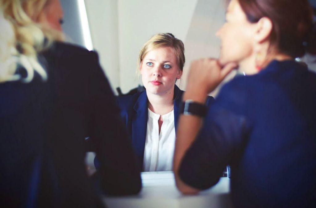une jeune fille blonde en entretien d'embauche face à deux recruteurs
